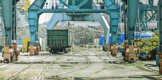 Σιδηροδρομικό βαγόνι εμπορευμάτων κάτω από τους γερανούς φόρτωσης στο θαλάσσιο λιμένα στοκ εικόνα