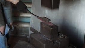 Σιδηρουργός που κρατά το candent πλίνθωμα σιδήρου και που σφυρηλατεί το που χρησιμοποιεί το πνευματικό σφυρί φιλμ μικρού μήκους
