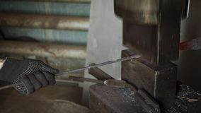 Σιδηρουργός που κρατά το candent πλίνθωμα σιδήρου και που σφυρηλατεί το που χρησιμοποιεί το πνευματικό σφυρί απόθεμα βίντεο