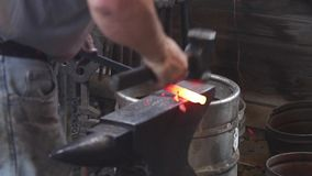 Σιδηρουργός που σφυρηλατεί τον καυτό σίδηρο στο αμόνι απόθεμα βίντεο