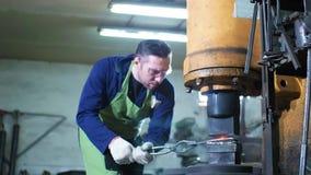Σιδηρουργός που σφυρηλατεί το καυτό αυτόματο σφυρί σιδήρου απόθεμα βίντεο