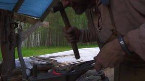 Σιδηρουργός που σφυρηλατεί το λειωμένο μέταλλο στο αμόνι στο σιδηρουργείο φιλμ μικρού μήκους