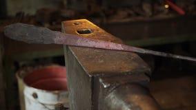 Σιδηρουργός που σφυρηλατεί το red-hot μέταλλο με το σφυρί απόθεμα βίντεο