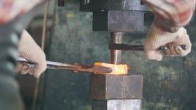 Σιδηρουργός στην εργασία με το ηλεκτρικό σφυρί στο αμόνι, που κάνει την τρύπα στο κόκκινο - καυτός χάλυβας, τέχνη απόθεμα βίντεο
