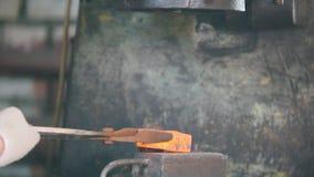Σιδηρουργός στην εργασία με το ηλεκτρικό σφυρί στο αμόνι, που κάνει τη σωστή μορφή του κοκκίνου - καυτός χάλυβας, τέχνη απόθεμα βίντεο
