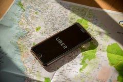 Σικάγο, IL, ΗΠΑ, FEB-12.2017, Smartphone με μια εφαρμογή Uber στην οθόνη και έναν χάρτη για την εκδοτική χρήση μόνο Στοκ Εικόνες