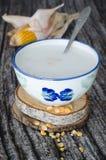Σιτάρια καλαμποκιού που μαγειρεύονται με το γάλα στο ηλικίας ξύλινο υπόβαθρο χαρακτηριστικός στοκ φωτογραφία με δικαίωμα ελεύθερης χρήσης