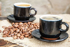 Σιτάρια καφέ σε έναν ξύλινο πίνακα και ένα φλιτζάνι του καφέ Στοκ Φωτογραφίες