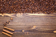 Σιτάρια του καφέ σε ένα καφετί ξύλινο υπόβαθρο με τα ραβδιά κανέλας Στοκ Φωτογραφία