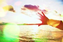 Σιτάρι ταινιών Η σκιαγραφία του χεριού και τα δάχτυλα προσπαθούν να αγγίξουν τον ήλιο, ηλιοβασίλεμα επάνω από τον ωκεανό Στοκ εικόνα με δικαίωμα ελεύθερης χρήσης