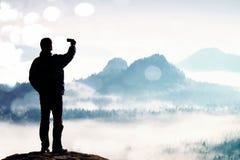 Σιτάρι ταινιών Ο ψηλός τουρίστας παίρνει selfie στην αιχμή επάνω από την κοιλάδα Έξυπνη τηλεφωνική φωτογραφία Στοκ Εικόνες