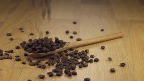 Σιτάρι των φασολιών καφέ που αφορούν το ξύλινο κουτάλι που βρίσκεται σε μια ξύλινη επιφάνεια απόθεμα βίντεο