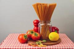 σιτηρέσιο έννοιας υγιει& Ολόκληρα μακαρόνια και λαχανικά σίτου στο κόκκινο τραπεζομάντιλο Στοκ Εικόνες