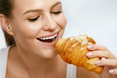 σιτηρέσιο Ευτυχής γυναίκα που τρώει Croissant για το πρόγευμα στοκ εικόνες με δικαίωμα ελεύθερης χρήσης