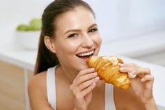 σιτηρέσιο Ευτυχής γυναίκα που τρώει Croissant για το πρόγευμα στοκ φωτογραφία