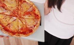 σιτηρέσιο Η έννοια της υγιούς κατανάλωσης, κρατά τη λιπαρή πίτσα κλιμάκων, υπερβολικό βάρος! Στοκ Φωτογραφία