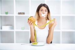 σιτηρέσιο Η γυναίκα πορτρέτου θέλει να φάει Burger αλλά κολλημένο skochem mou στοκ φωτογραφία με δικαίωμα ελεύθερης χρήσης