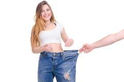 σιτηρέσιο Ικανότητα Νέο κορίτσι στο μεγάλο μέγεθος τζιν παντελόνι σε ένα άσπρο υπόβαθρο Στοκ Εικόνα