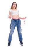 σιτηρέσιο Ικανότητα Νέο κορίτσι στο μεγάλο μέγεθος τζιν παντελόνι σε ένα άσπρο υπόβαθρο Στοκ Φωτογραφίες