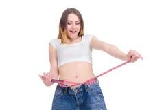 σιτηρέσιο Ικανότητα Νέο κορίτσι στο μεγάλο μέγεθος τζιν παντελόνι σε ένα άσπρο υπόβαθρο Στοκ Εικόνες