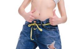 σιτηρέσιο Ικανότητα Νέο κορίτσι στο μεγάλο μέγεθος τζιν παντελόνι σε ένα άσπρο υπόβαθρο Στοκ Φωτογραφία