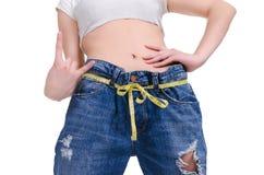 σιτηρέσιο Ικανότητα Νέο κορίτσι στο μεγάλο μέγεθος τζιν παντελόνι σε ένα άσπρο υπόβαθρο Στοκ εικόνα με δικαίωμα ελεύθερης χρήσης