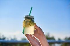 σιτηρέσιο κατανάλωση υγιής Ποτό λεμονάδας εκμετάλλευσης χεριών γυναικών στη θολωμένη υπόβαθρο φύση υπαίθρια Φρέσκος φυτικός χυμός Στοκ φωτογραφία με δικαίωμα ελεύθερης χρήσης
