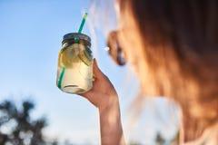 σιτηρέσιο κατανάλωση υγιής Ποτό λεμονάδας εκμετάλλευσης χεριών γυναικών στη θολωμένη υπόβαθρο φύση υπαίθρια Φρέσκος φυτικός χυμός Στοκ εικόνα με δικαίωμα ελεύθερης χρήσης