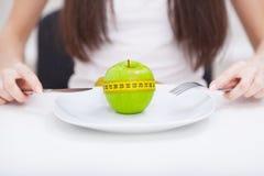 σιτηρέσιο Κλείστε επάνω τη φωτογραφία του μέτρου ταινιών που κουλουριάζεται γύρω από ένα μήλο στο W Στοκ Φωτογραφίες