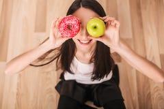 σιτηρέσιο Μια νέα γυναίκα που κρατά μια πίτσα στις κλίμακες και κάνει μια επιλογή μεταξύ ενός μήλου και doughnut κατανάλωση έννοι Στοκ Φωτογραφία