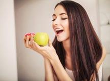 σιτηρέσιο Μια νέα γυναίκα που κρατά μια πίτσα στις κλίμακες και κάνει μια επιλογή μεταξύ ενός μήλου και doughnut κατανάλωση έννοι Στοκ φωτογραφία με δικαίωμα ελεύθερης χρήσης