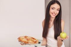 σιτηρέσιο Μια νέα γυναίκα που κρατά μια πίτσα στις κλίμακες κατανάλωση έννοιας υγιής Στοκ Φωτογραφίες