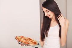 σιτηρέσιο Μια νέα γυναίκα που κρατά μια πίτσα στις κλίμακες κατανάλωση έννοιας υγιής Στοκ Φωτογραφία