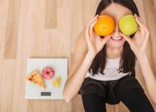 σιτηρέσιο Μια νέα γυναίκα που κρατά μια πίτσα στις κλίμακες κατανάλωση έννοιας υγιής Στοκ Εικόνα