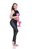 σιτηρέσιο Νέο όμορφο κορίτσι με τους ρόδινους αλτήρες στα χέρια του Το κορίτσι εκτελεί την αθλητική άσκηση Στοκ Φωτογραφία