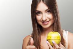 σιτηρέσιο Το νέο κορίτσι ικανότητας Α εμμένει σε μια διατροφή και κρατά ένα μήλο Στοκ Εικόνες