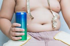 σιτηρέσιο Το παχύσαρκο παχύ αγόρι που κρατά το μη αλκοολούχο ποτό μπορεί Στοκ Φωτογραφίες
