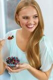 σιτηρέσιο υγιεινό Γυναίκα που τρώει τα δημητριακά, μούρα το πρωί διατροφή στοκ φωτογραφίες