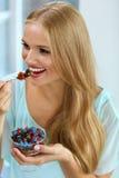 σιτηρέσιο υγιεινό Γυναίκα που τρώει τα δημητριακά, μούρα το πρωί διατροφή στοκ εικόνες