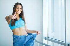 σιτηρέσιο Όμορφη νέα γυναίκα με τα μεγάλα τζιν στοκ εικόνες με δικαίωμα ελεύθερης χρήσης
