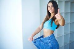 σιτηρέσιο Όμορφη νέα γυναίκα με τα μεγάλα τζιν στοκ εικόνα με δικαίωμα ελεύθερης χρήσης