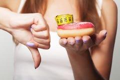 σιτηρέσιο Doughnut αριθ. Ένα νέο κορίτσι κρατά doughnut σε ετοιμότητα της και παρουσιάζει Στοκ εικόνες με δικαίωμα ελεύθερης χρήσης