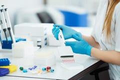 Σιφώνιο που ρίχνει ένα δείγμα σε έναν σωλήνα δοκιμής Εργαστηριακός βοηθός που αναλύει το αίμα στο εργαστήριο Ανάλυση DNA στοκ εικόνα με δικαίωμα ελεύθερης χρήσης