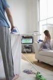 Σιδέρωμα και κόρη ατόμων στον καναπέ από την τηλεόραση στοκ φωτογραφία