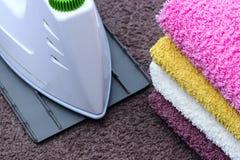 Σιδέρωμα του λινού με τη γεννήτρια ατμού Ένας σωρός των σιδερωμένων πετσετών που βρίσκονται δίπλα στο σίδηρο Τεφλόν μόνο πιάτο πο στοκ εικόνα με δικαίωμα ελεύθερης χρήσης