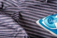 Σιδέρωμα του πουκάμισου ατόμων στα λωρίδες Στοκ φωτογραφία με δικαίωμα ελεύθερης χρήσης