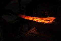 Σιδηρουργός που εργάζεται σε ένα κομμάτι του μετάλλου στοκ φωτογραφίες