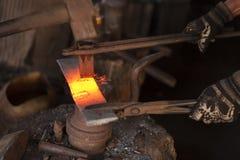 Σιδηρουργός που κόβει ένα κομμάτι του μετάλλου στοκ φωτογραφίες