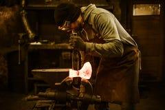 Σιδηρουργός που σφυρηλατεί το λειωμένο μέταλλο στη σκουριασμένη μέγγενη στο σιδηρουργείο στοκ εικόνα με δικαίωμα ελεύθερης χρήσης