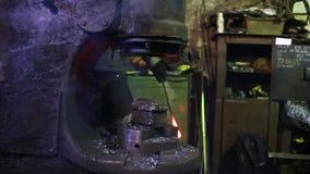 Σιδηρουργός που σφυρηλατεί το καυτό αυτόματο σφυρί σιδήρου φιλμ μικρού μήκους